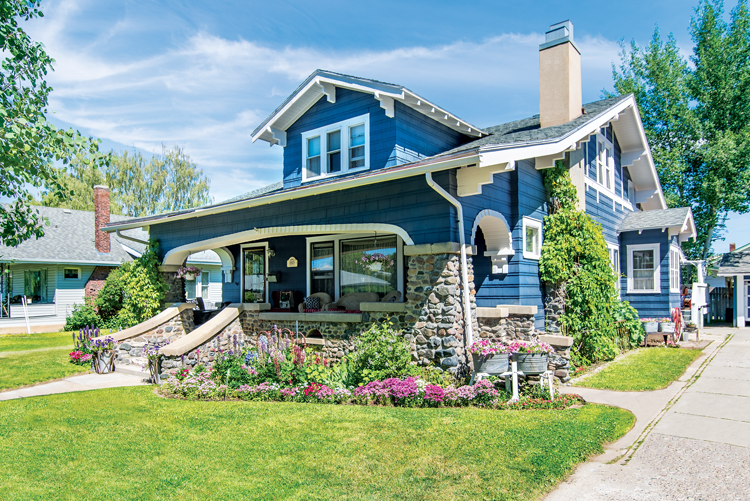 A 1920s craftsman style home in a bold blue color with a stone porch.