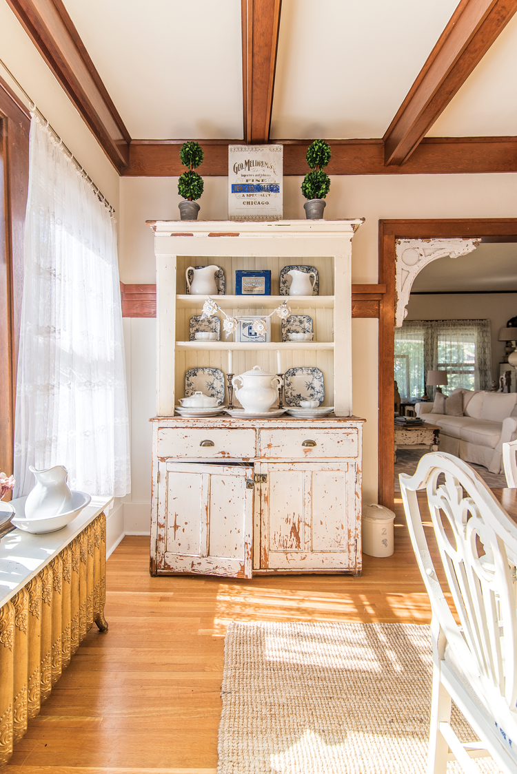 A white rustic, distressed hutch near an original radiator with an exposed wooden ceiling beams.
