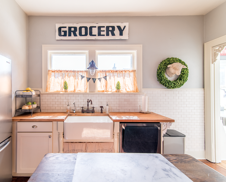 "Butcher block countertops and a bright white backdrop set the kitchen scene with an antique ""grocery"" sign mounted above the farmhouse sink."