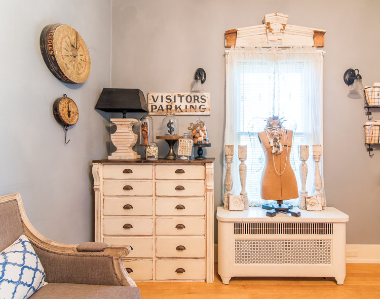 A guest room with a vintage white painted dresser and a wooden mannequin surrounded by candlesticks.