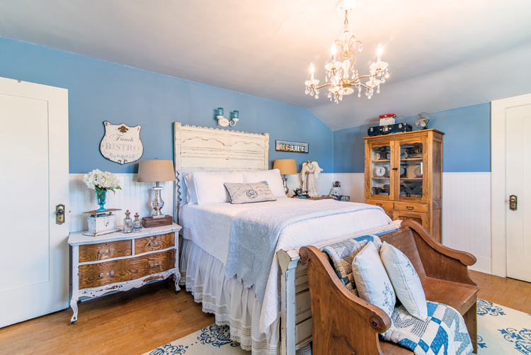 Charming farmhouse inspired bedroom with white and blue accents, a crystal chandelier, and a restored wooden church pew at the foot of the bed.