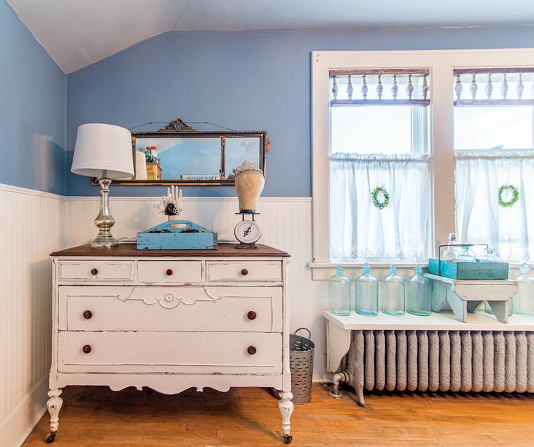 A found antique mirror hanging above a vintage detailed white dresser near bright craftsman style windows.