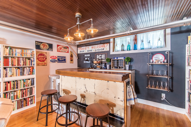 A bar set up in the basement covered with tin ceiling tiles with vintage-style barstools.