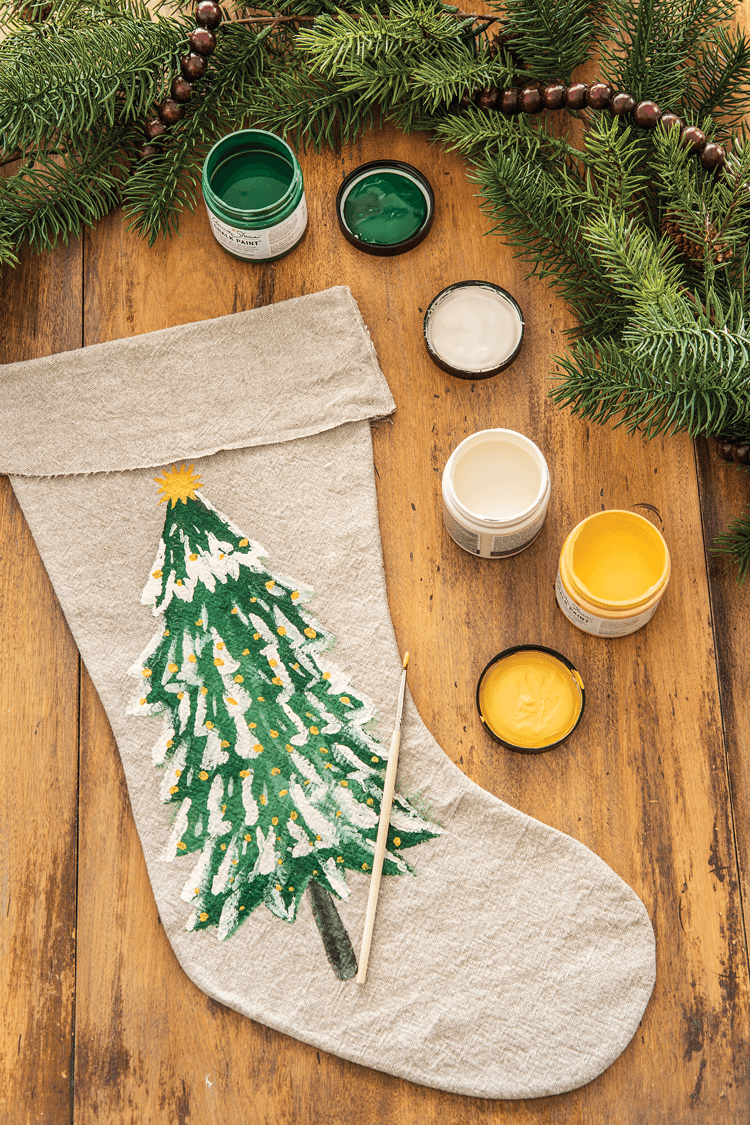 Hand painted DIY Christmas stocking with Christmas tree picture and paint pots around it