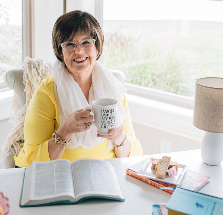 Debbie Macomber sits at a desk