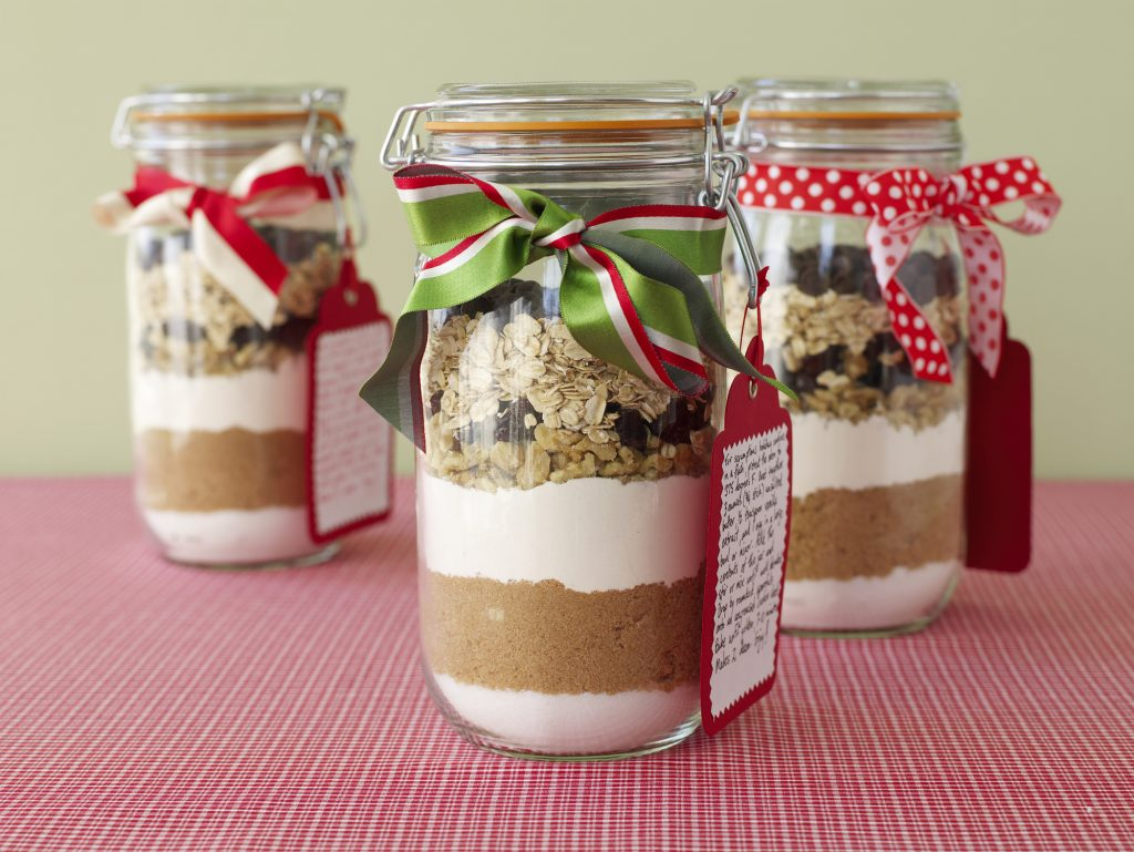 cookie ingredients nicely layered in a jar topped with christmas ribbon and a recipe tag