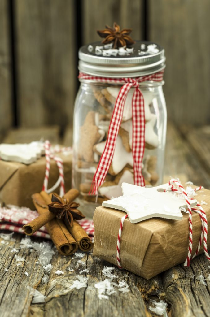iced cinnamon sugar cookies shaped like stars in a jar tied with red and white checked ribbon ready to be gifted