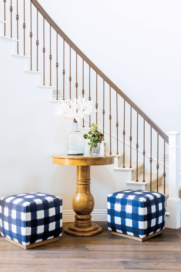 Two navy blue large check gingham ottomans placed next to a small wooden pedestal table at the foot of a staircase.