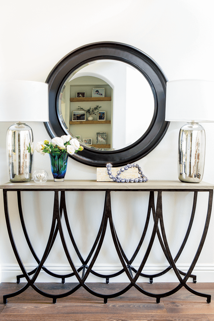 An ornate entryway table with black metallic base and a stone surface topped with symmetrical mercury glass lamps framing a large circular wall-mounted mirror.