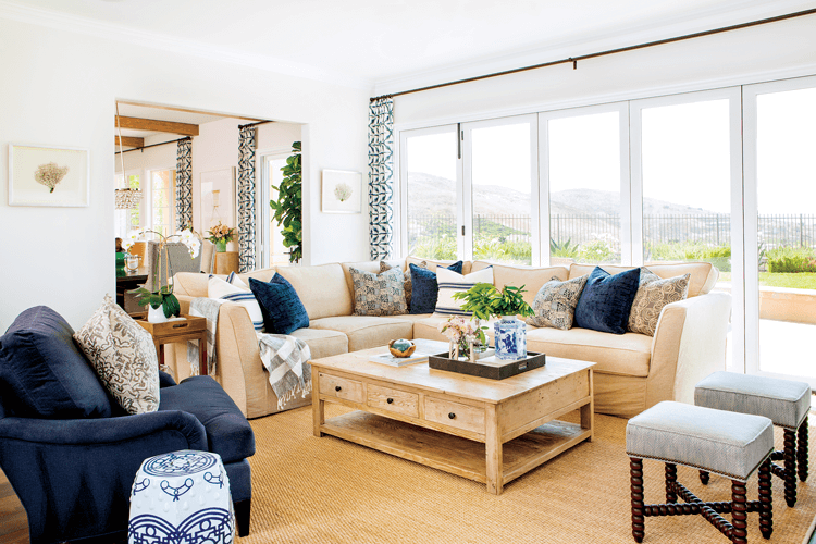 Living room with a full wall of fold-away windows, filled with a large sand colored sectional, wooden coffee table and navy blue armchair.