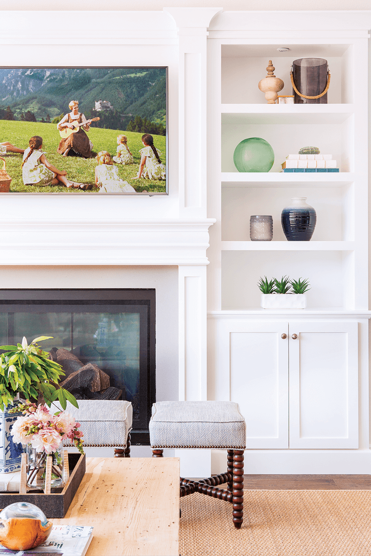 A large framed print from the Sound Of Music placed over the fireplace and surrounded by bright white built-ins.