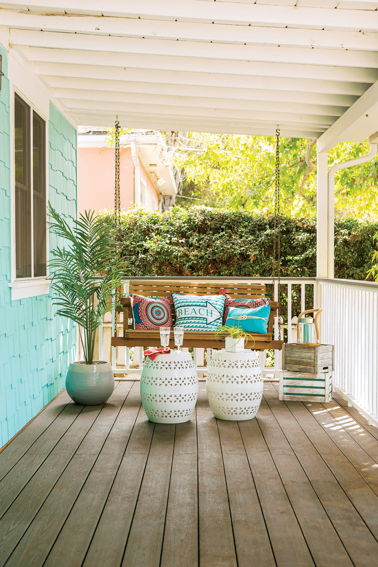 Wooden slatted front porch with white railing and a swinging wooden bench swing with colorful beach inspired pillows and accents.