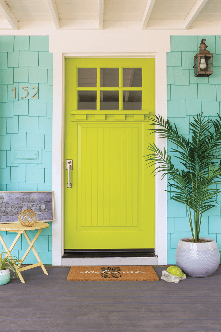 Vibrant chartreuse colored front door with white trim against a coastal inspired blue exterior paint for a charming home entry.