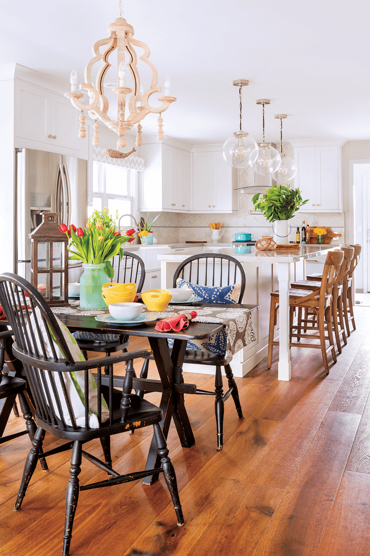 Distressed dark wooden farmhouse chairs and dining table covered in bright and colorful tulips. Looking into an open concept white and bright colorful beach cottage kitchen.