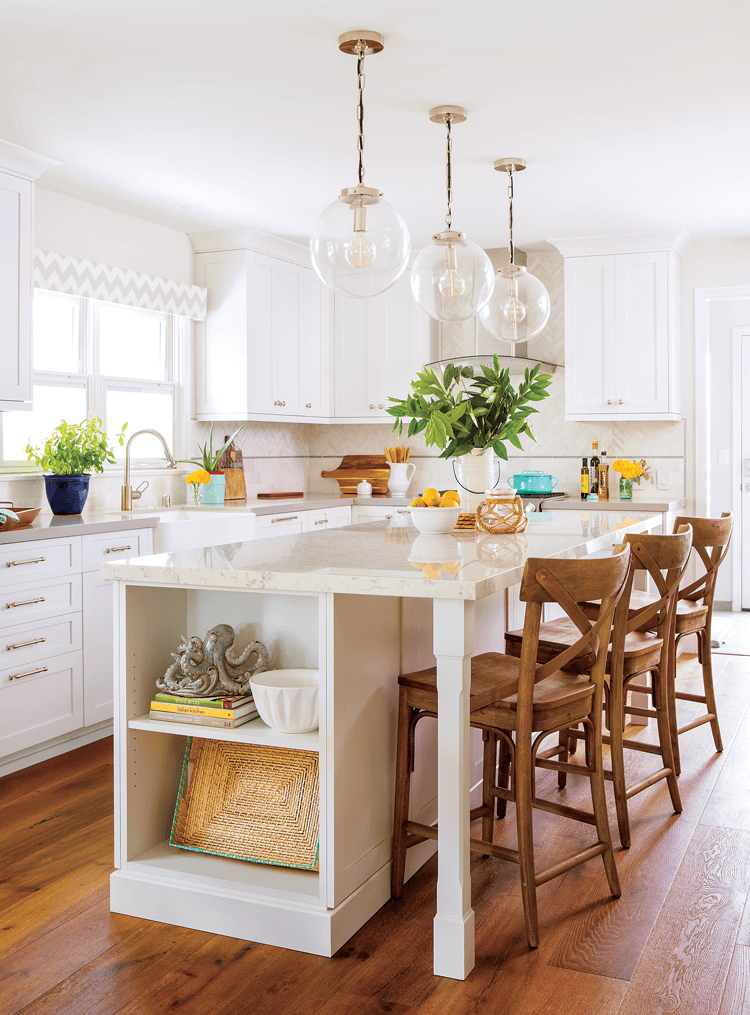 Marble topped large kitchen island in the center of a white and bright kitchen accented by globe pendant lights and fresh greenery.