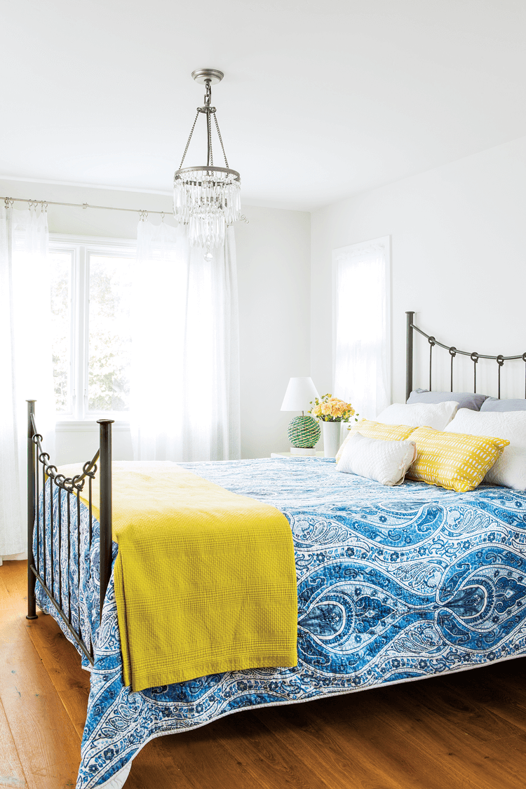 Bright and colorful beach cottage bedroom, white walls with a crystal chandelier and a bright blue quilt on the rod-iron bed.