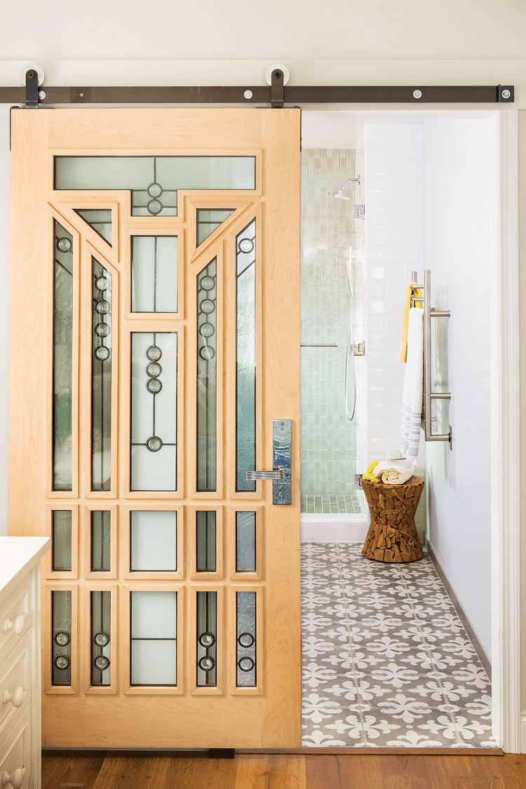 An arts and crafts style glass and wooden barn door makes such a statement as you walk toward the bathroom.