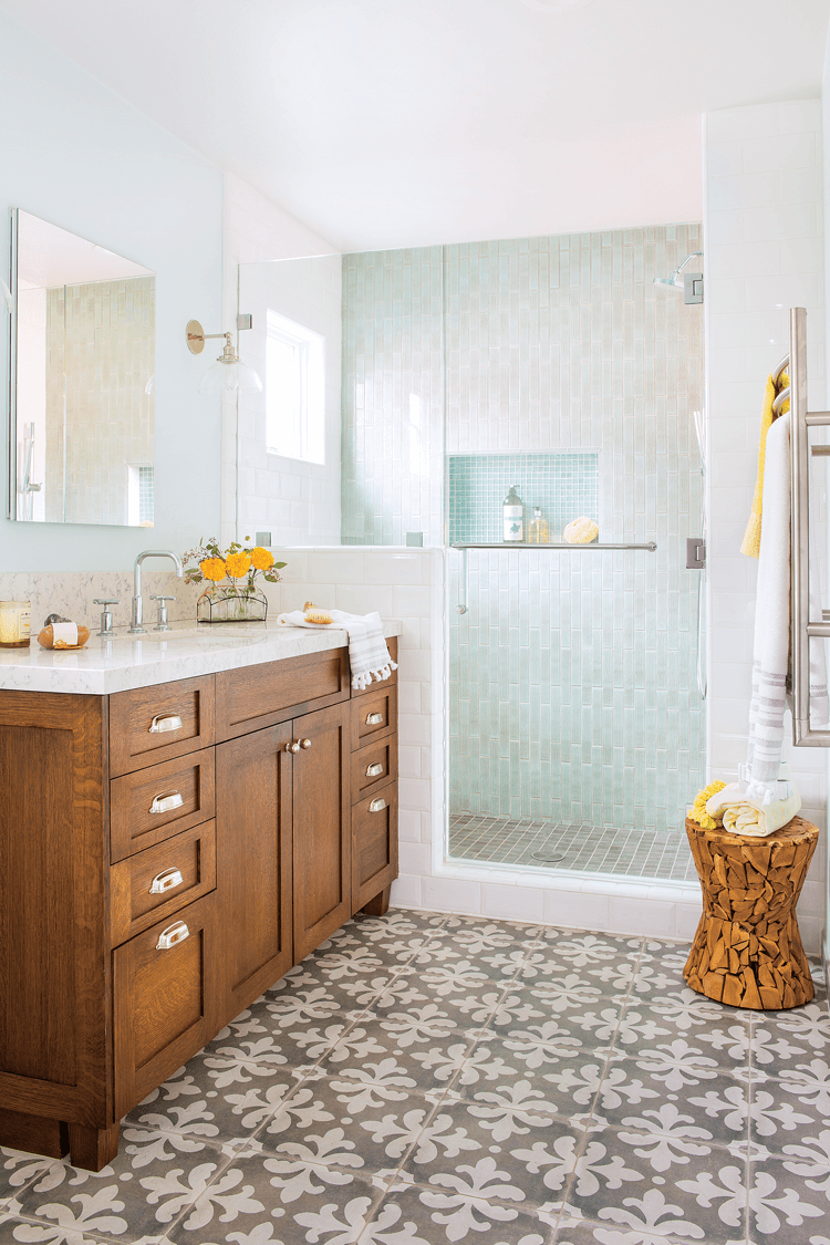 Wooden vanity in a bathroom, open concept tiled shower and faux-cement tiled floors with an intricate pattern.