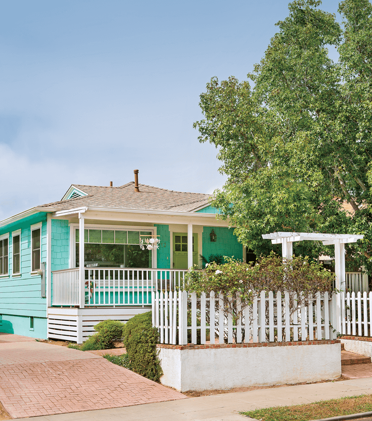 White picket fences and a bright blue exterior bring this charming beach cottage to life.