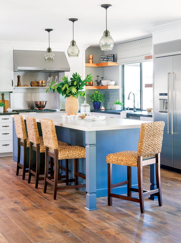 An open-concept kitchen with a large blue island with crisp white countertop and Routan bar height chairs.