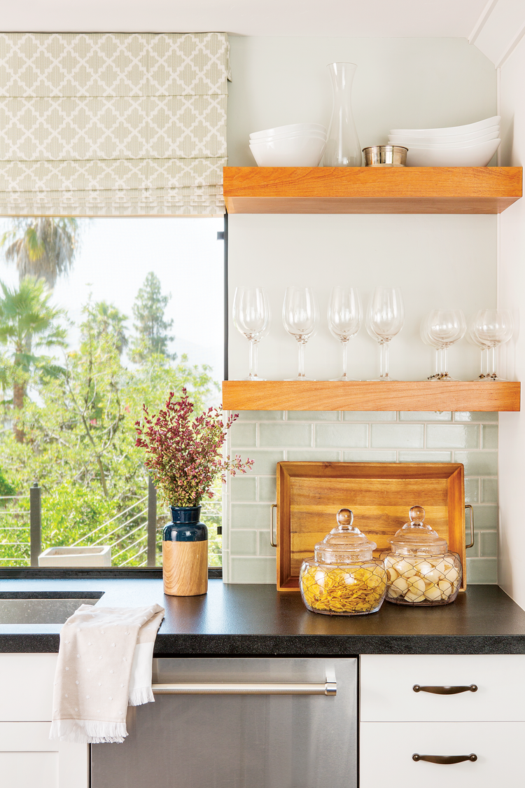 Light and airy backdrop that suits this open shelving with a pop of bold back granite countertops.