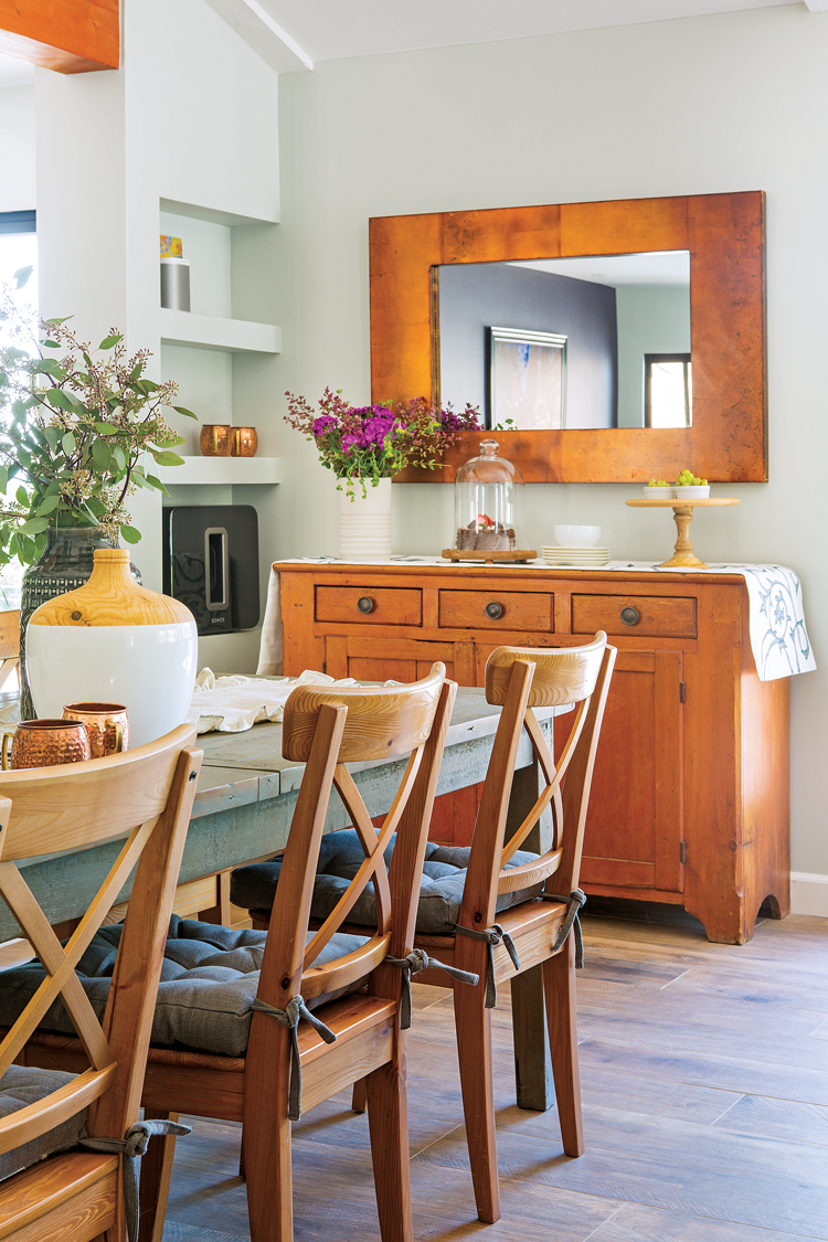 Rustic dining area with a warm wood toned sideboard beneath a rectangular mirror.