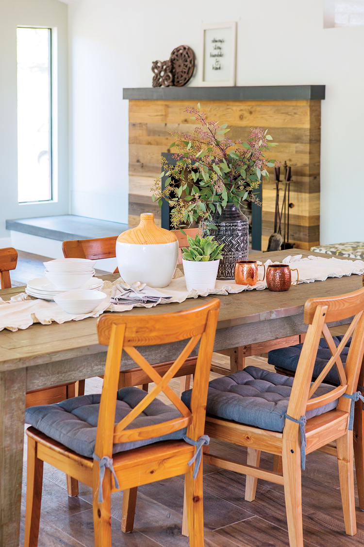 A view from the open-concept kitchen that spans across the rustic dining table and into the living space.