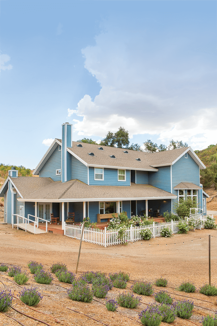 A custom designed farmhouse painted a shade of eggshell blue surrounded by a lovely garden and a white picket fence.