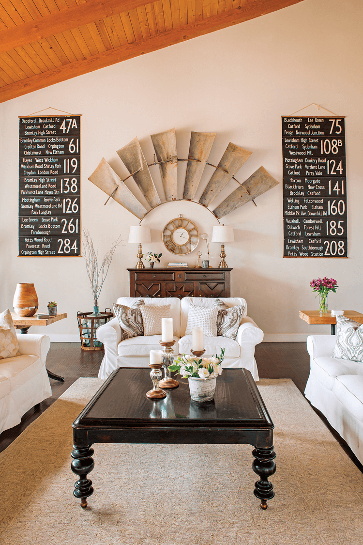 Vaulted exposed wood ceilings in an all white room with covered sofas. Large windmill pieces mounted on the wall and a bold, black farmhouse coffee table.