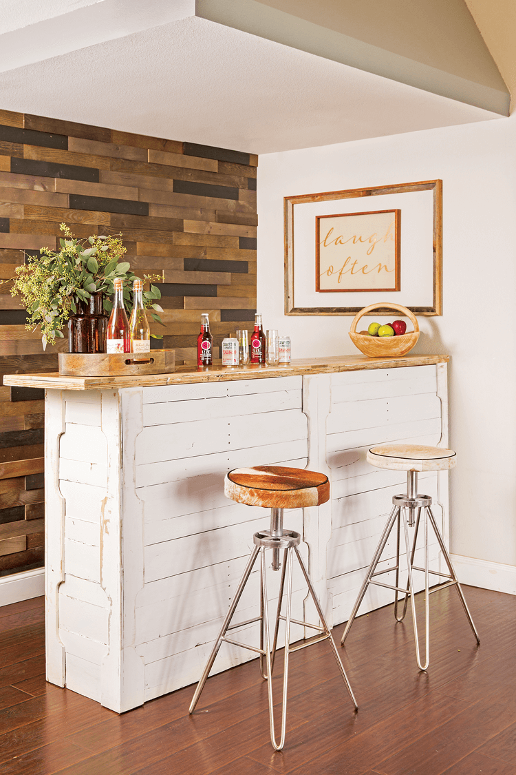 Modern hair-pinned leg barstools sitting at a rustic indoor bar. The bar is covered in white reclaimed shiplap and the accent wall behind it is also made of darker reclaimed wood pieces.
