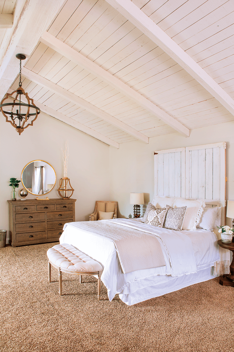 An all white, rustic style bedroom complete with exposed, vaulted ceilings and warm wooden accents like the dresser and chandelier.