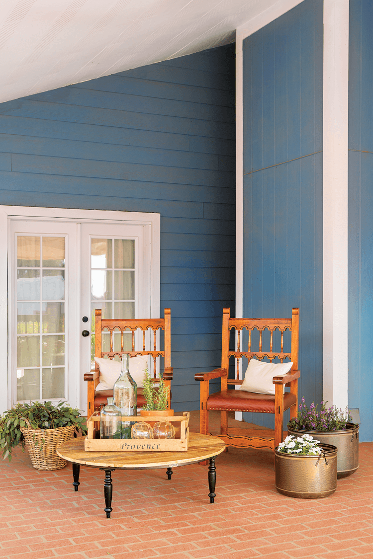 Beautiful French doors leading into the house from the porch. Ornate wooden chairs for a small seating area surrounded by basket and metallic planters.