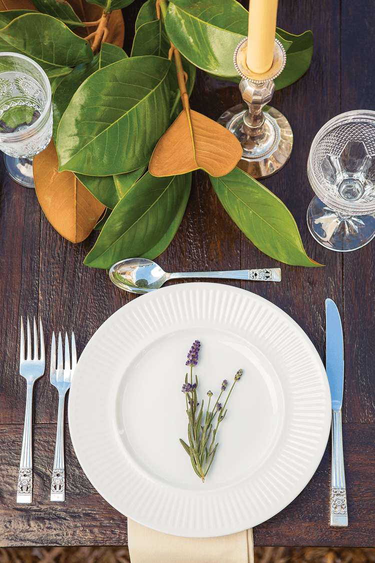 A simple table setting with silver flatware, white and crystal elements, and garnished with lavender and magnolia branches.