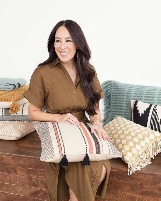 Joanna Gaines sitting amongst her newest textiles and pillows from her collection.