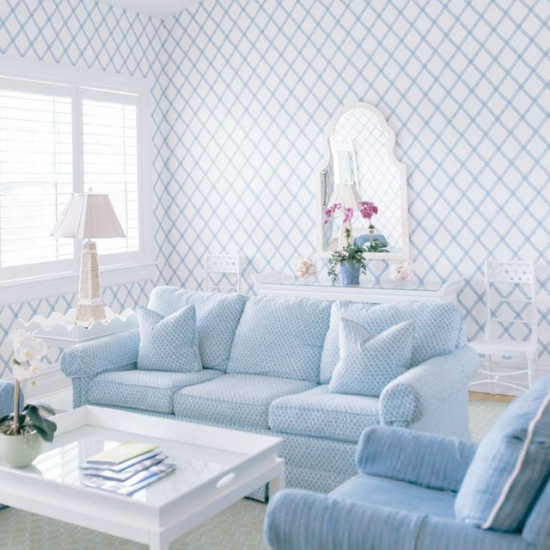 Bright white room with blue linen accents. Light blue sofa, armchair and a white coffee table and end table.