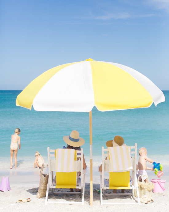 White and yellow beach umbrella shading two adults in beach chairs and surrounded by 3 small children playing in the sand.