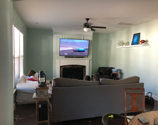 Before photo of a living room, tv above the fireplace and dark colored furniture.