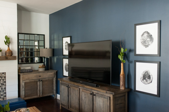 Deep blue accent wall with the television over a wooden cabinet.