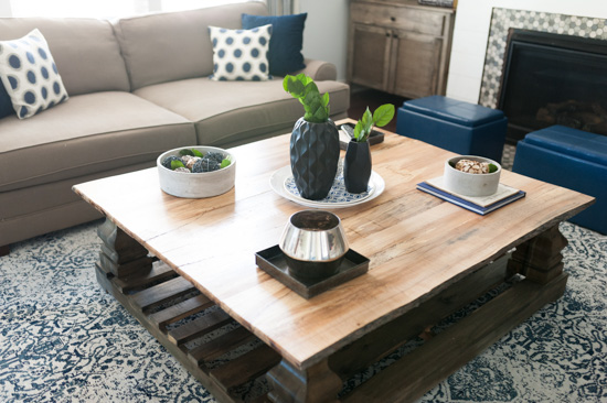 Wooden, square coffee table with potted plants and vases.