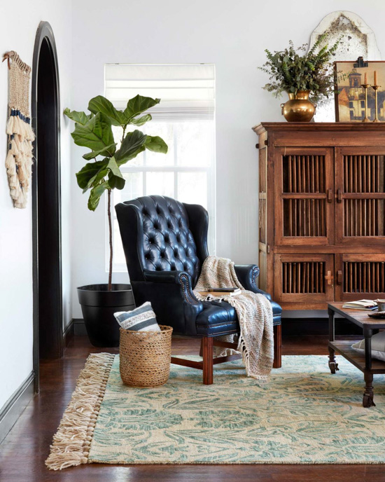 Black, tufted, leather wingback chair in front of a fiddle-leaf fig tree, showing off an aqua area rug from the new magnolia home collection.