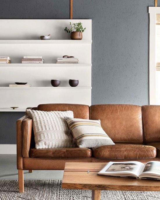 Leather brown couch with decorative pillows in front of modern white bookshelf.