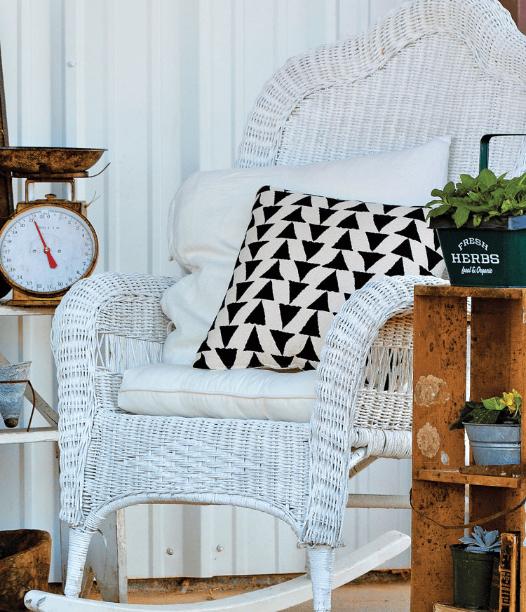 vintage wicker chair with black and white pillow