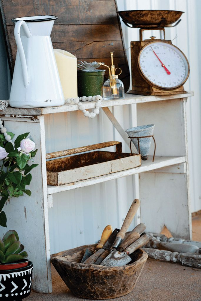 vintage bookshelf styled with an old enamel pitcher, vintage scale and vintage garden items