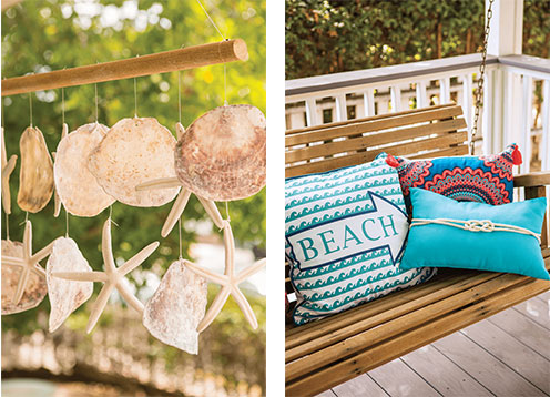 Hanging sand dollar and starfish wind chime and bright throw pillows on the wooden bench swing.