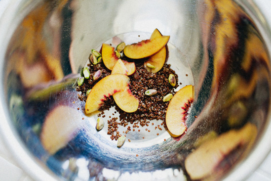 Looking inside a silver mixing bowl at nectarines, pistachios and quinoa.