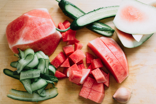 Cutting board covered in pieces of brightly colored watermelon and cucumber.
