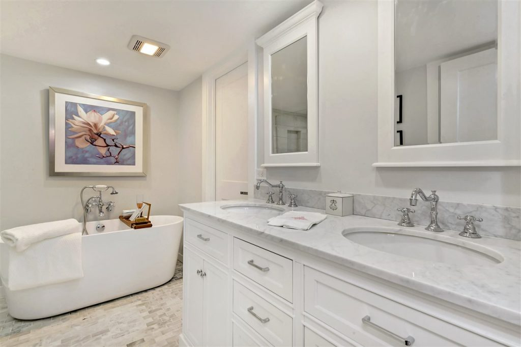 updated cottage master bath suite with modern freestanding tub, white carera marble tile floors and countertop