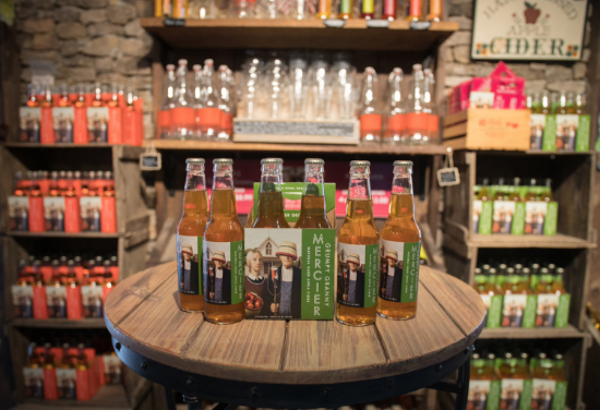 A rustic display of cider bottles in a few different varieties with a stone wall in the background.