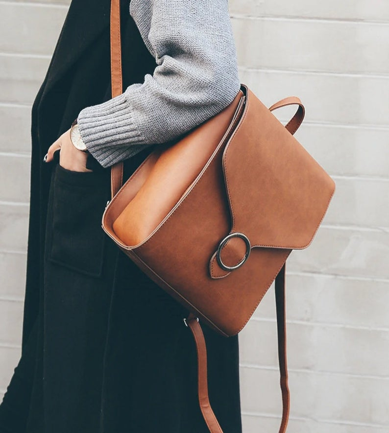 Woman in black jumper with chunky knit gray cardigan modeling a brown leather purse that also converts to a backpack.