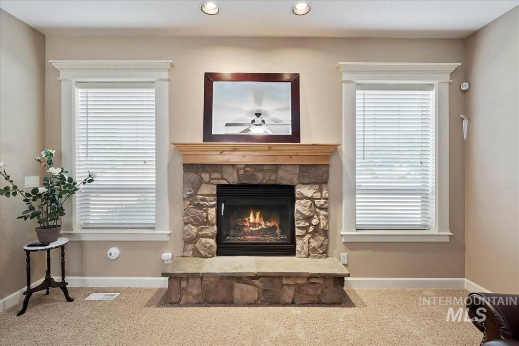 stone fireplace with wood mantel flanked by casement windows